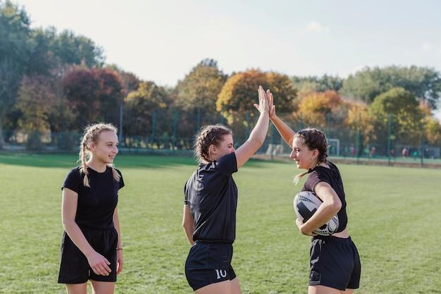 Esportivas meninas segurando uma bola de futebol e mais cinco