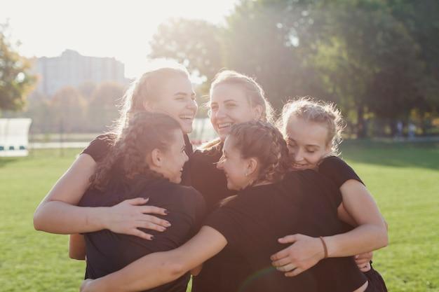 Esportivas mulheres abraçando em um campo de futebol