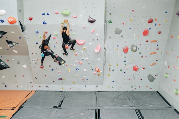 Esportivas pessoas malhando na parede de escalada