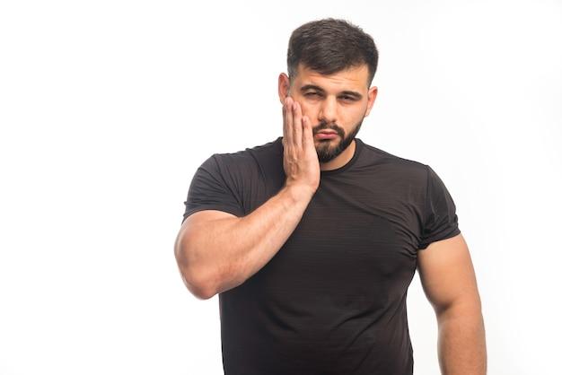 Esportivo homem de camisa preta, colocando a mão na bochecha.