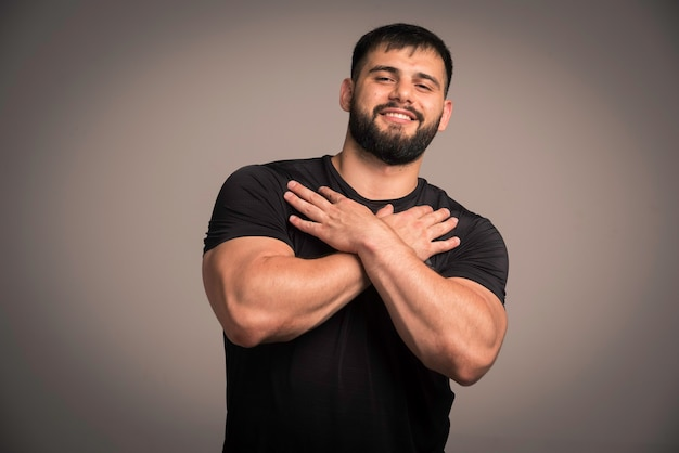 Esportivo homem de camisa preta, cruzando as mãos no peito.