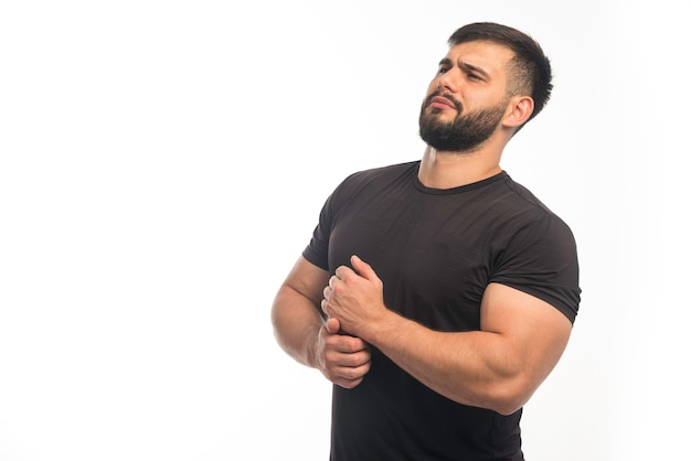 Esportivo homem de camisa preta, demonstrando os músculos do braço.