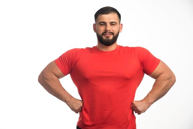 Esportivo homem de camisa vermelha, demonstrando os músculos do braço e parece confiante.