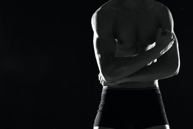 Esportivo homem musculoso em shorts pretos fisiculturista fundo escuro