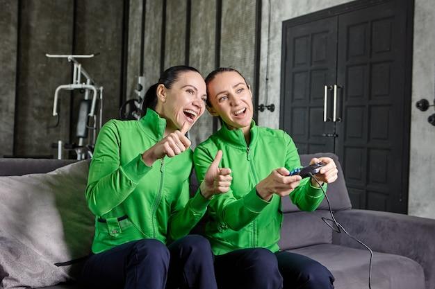 Esports para mulheres ou cybersport para mulheres, treinos de equipe em apartamento loft usando console de jogo.