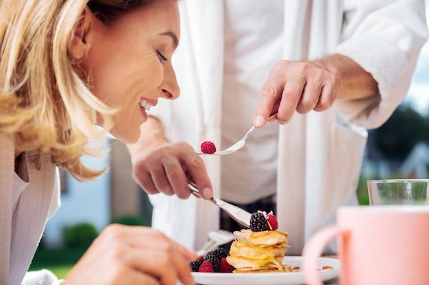 Esposa alimentando. marido amoroso de pijama alimentando sua linda esposa loira enquanto toma café da manhã fora de casa