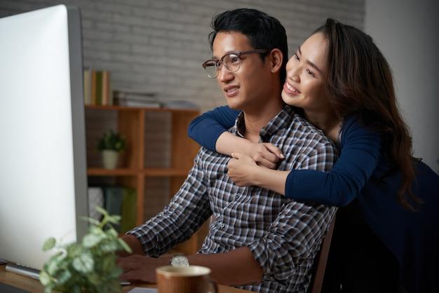 Esposa amorosa, abraçando o marido pelas costas enquanto ele trabalha no computador