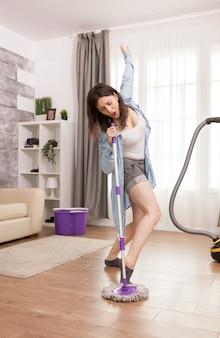 Esposa animada cantando enquanto esfrega o chão do apartamento