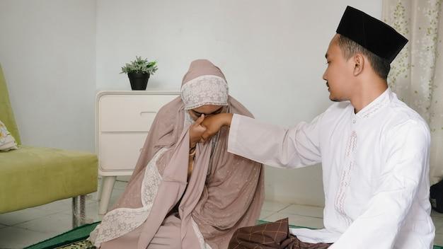 Esposa beijando a mão do marido após o culto juntos em casa