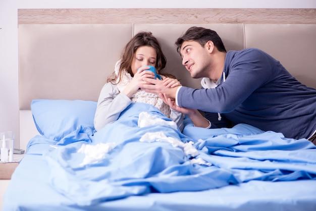 Esposa cuidando do marido doente em casa na cama