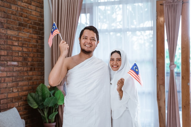 Esposa e marido asiáticos segurando a bandeira nacional da malásia