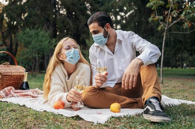 Esposa e marido fazendo um piquenique usando máscaras médicas