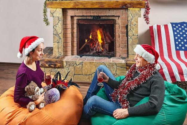 Esposa e marido usando chapéus de papai noel estão bebendo em pufes enquanto comemoram o ano novo.