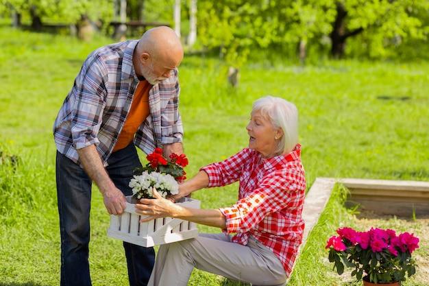 Esposa falando. marido e mulher de cabelos grisalhos conversando enquanto colocam vasos de flores na caixa branca