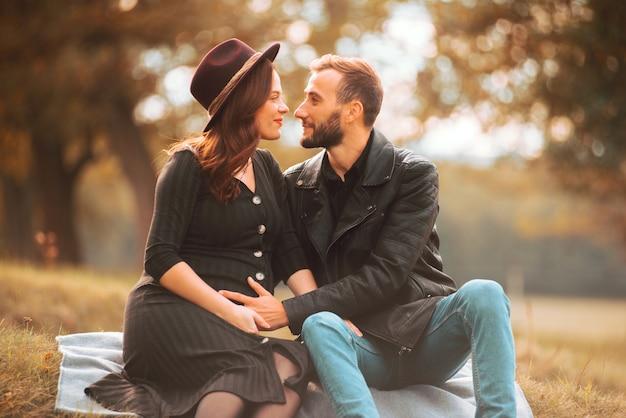 Esposa grávida e seu marido no parque