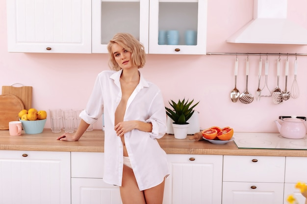 Esposa jovem. mulher jovem bonita e sexy usando calcinha branca e camisa em pé na cozinha