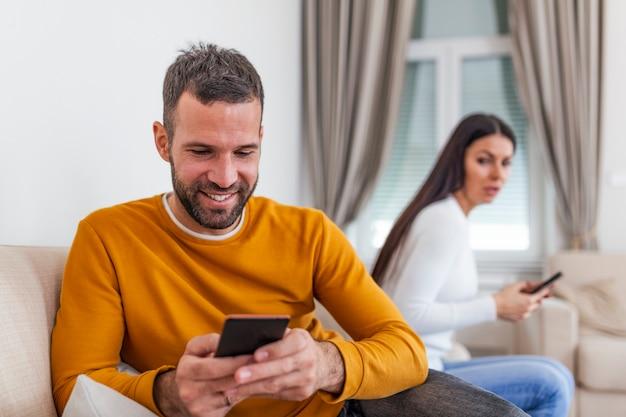 Esposa louca e suspeita ciumenta com o marido segurando o telefone trocando mensagens de texto