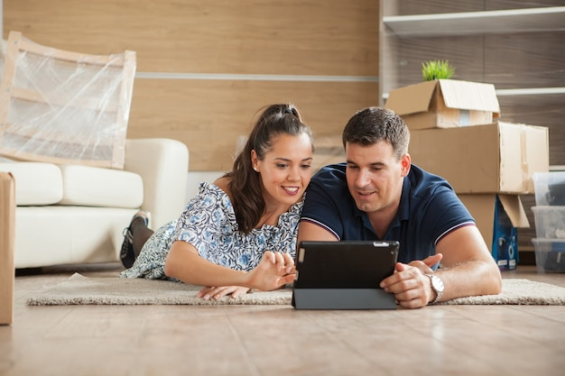 Esposa mostrando ao marido a cama para seu novo apartamento em seu tablet