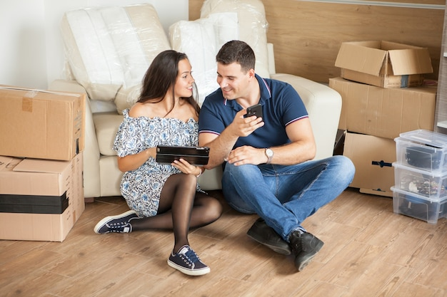 Esposa mostrando ao marido as novas cortinas de seu tablet. casal criando memórias