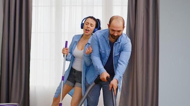 Esposa ouvindo música no fone de ouvido e limpando o chão com o esfregão enquanto o marido está usando o aspirador de pó