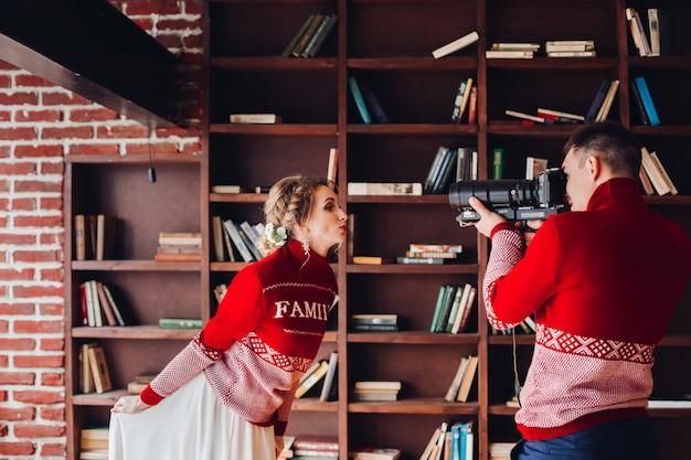 Esposa posando para o marido tirando fotos dela sobre estantes de livros