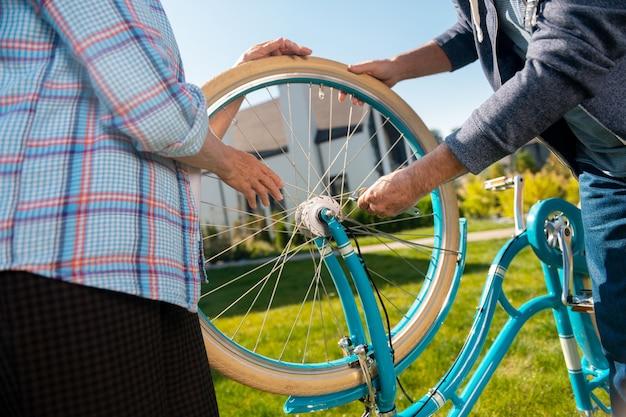 Esposa prestativa. esposa prestativa e de bom coração, vestindo uma camisa quadrada azul, ajudando o marido a consertar uma bicicleta