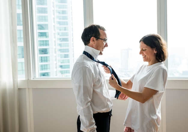 Esposa que ajuda amarrar o laço dos maridos