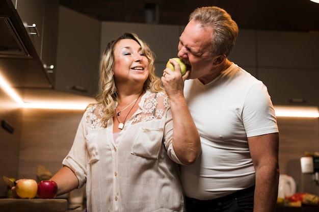 Esposa que alimenta a maçã ao marido sênior