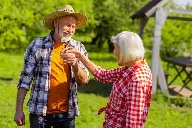 Esposa se sentindo surpresa. esposa grisalha se sentindo surpresa ao receber dente-de-leão de seu amado marido