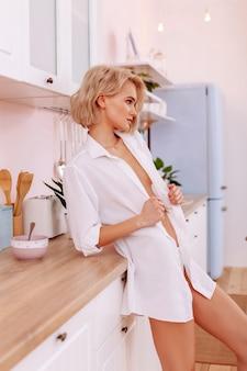 Esposa sexy. jovem mulher sexy vestindo calcinha branca e camisa esperando pelo marido na cozinha