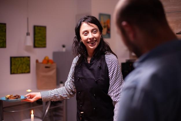 Esposa sorrindo para o marido usando avental, enquanto olha para o marido depois de preparar um jantar saboroso. mulher cozinhando comida festiva para ela e o marido para celebrar o relacionamento e o romance, felicidade, positivo, lo