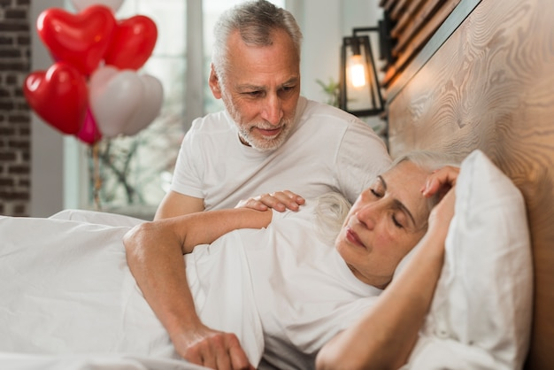 Esposa surpreendente de homem sênior na cama