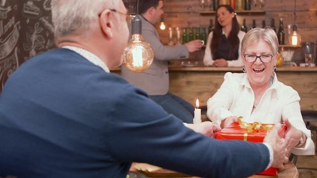 Esposa surpreendida pelo marido com uma caixa de presente na hora das refeições. casal relaxado. casal feliz sênior.
