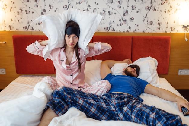 Esposa tapando os ouvidos, marido ronca no quarto, sono ruim
