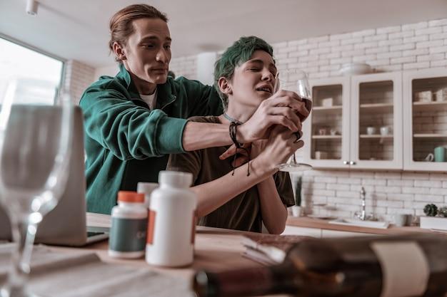 Esposa viciada. marido amoroso preocupado tomando álcool de sua esposa de cabelos verdes viciada nisso
