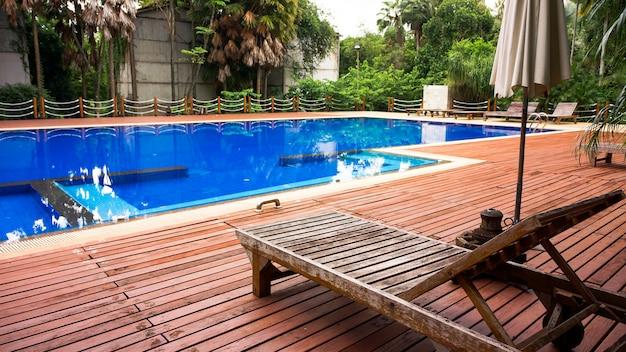 Espreguiçadeira de madeira com guarda-chuva na piscina moderna