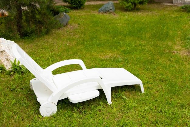 Espreguiçadeira de plástico branco em um gramado verde