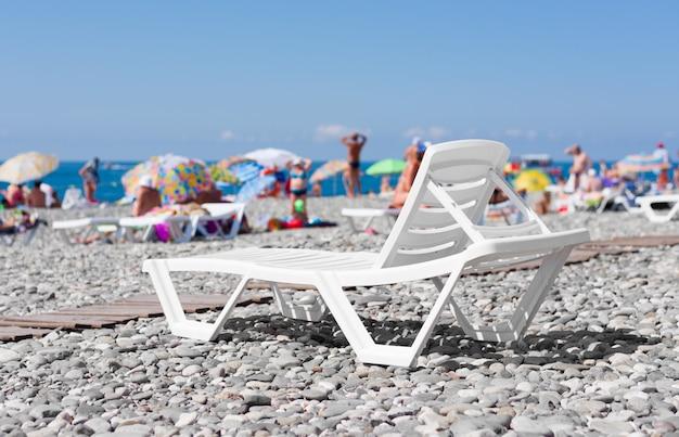 Espreguiçadeira de plástico branco na praia à beira-mar ao fundo de pessoas tomando banho de sol