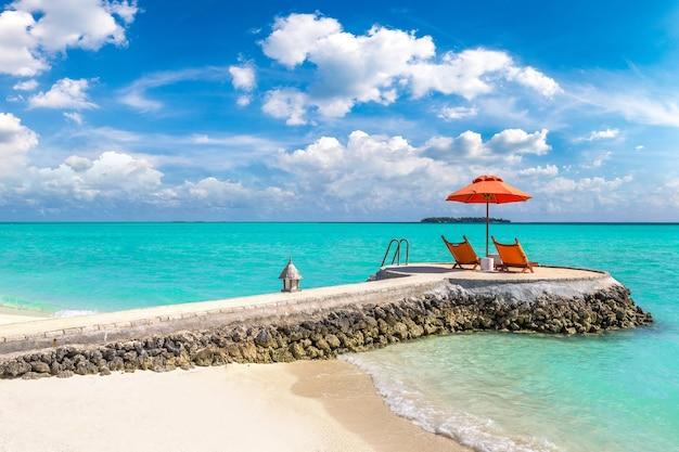 Espreguiçadeira e guarda-sol em praia tropical nas maldivas