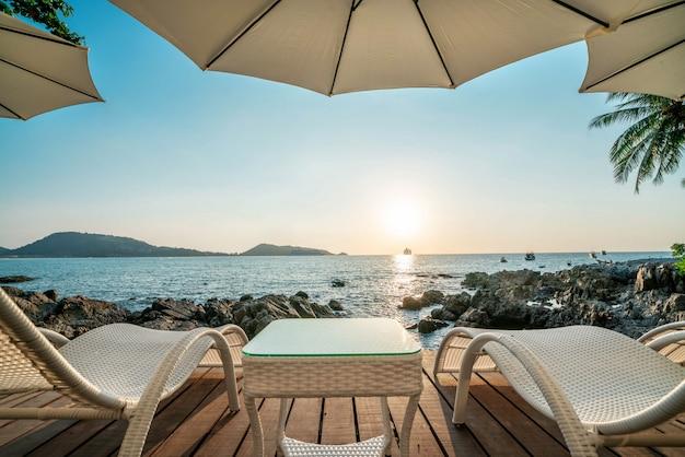 Espreguiçadeira na praia com belo pôr do sol no oceano