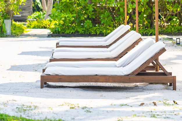 Espreguiçadeira vazia ao redor da piscina externa em hotel resort para férias de lazer