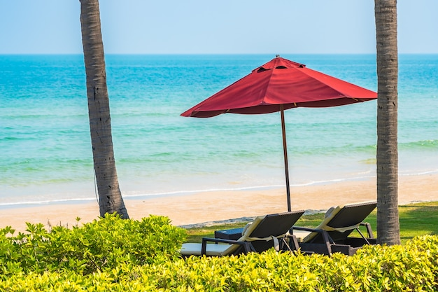 Espreguiçadeira vazia com guarda-chuva no céu azul do mar da praia para viagens de lazer