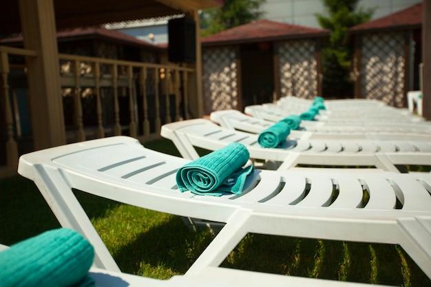 Espreguiçadeiras brancas de verão à beira da piscina no verão
