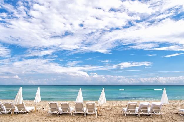 Espreguiçadeiras brancas de verão e guarda-sóis fechados em fila na costa vazia do oceano com areia e céu azul nublado em south beach, miami, flórida