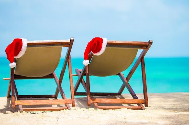 Espreguiçadeiras com chapéu de papai noel na bela praia tropical com areia branca e água azul-turquesa.