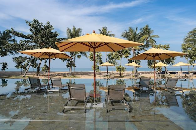 Espreguiçadeiras com guarda-chuva amarelo na piscina do hotel resort tropical perto da praia.