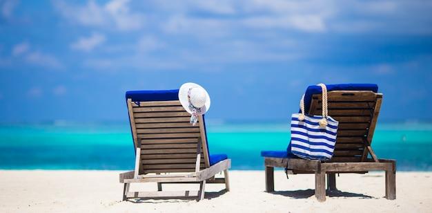 Espreguiçadeiras com saco e chapéu na praia tropical branco