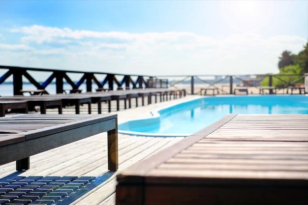 Espreguiçadeiras de madeira à beira da piscina. perto do mar.