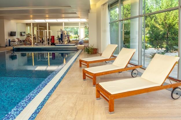 Espreguiçadeiras de madeira na piscina interna da casa com árvores coníferas verdes como pano de fundo atrás da janela