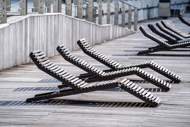 Espreguiçadeiras de madeira vazias no passeio na baía da marina de singapura